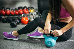 Side picture of woman wearing sportswear with kettlebell