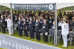 Attendees pay respects to the Korean national anthem during a ceremony at the United Nations Cemetery in Busan commemorating the 70th anniversary of the outbreak of the Korean War.