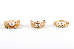 Three crown-shaped rings with stones on a white background