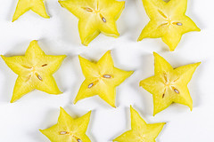 Carambola pieces-yellow stars on a white background, top view