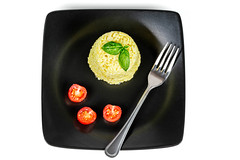 Top view, rice with tomatoes and basil in a black plate on a white background