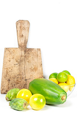 Exotic fruit on a white background with old kitchen board. Yellow passion fruit, papaya, cactus fruit, limes and lemons