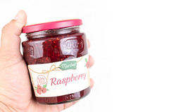 Raspberry Jam in the jar with copy space above white background