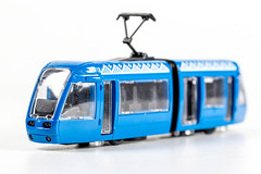 Toy blue tram on white background
