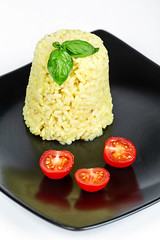 Boiled rice with slices of tomatoes and basil leaves on a black plate
