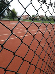 Closeup view on green metal fence of tennis court