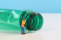 Miniature cleaning worker with empty plastic bottle
