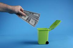 Man throwing away dollars in trashcan