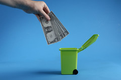 Male hand throwing bundle of money dollars into green trash bin on blue background
