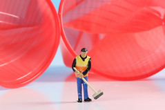 Miniature cleaning worker with empty red plastic cups