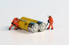 Two miniature workers with yellow alkaline batteries