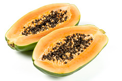 Half cut ripe papaya with seed on white background