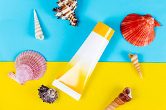 Tube of sunscreen with shells on a yellow and blue background. Beach vacation concept, top view