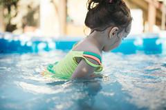 Little girl have fun in the swiming pool.