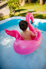Beautiful little girl floating on a flamingo float in a colorful swimming poo.