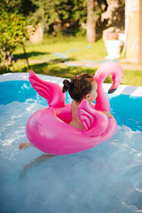 Beautiful little girl floating on a flamingo float in a swimming pool.