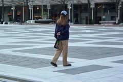 Woman walking across Freedom Plaza