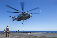 Marines fast-rope out of a CH-53E Super Stallion helicopter onto USS Bataan (LHD 5).