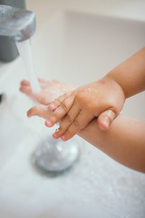 Child washing hands closeup.