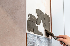 Workman apply a trowel on the wall mixture for gluing tiles
