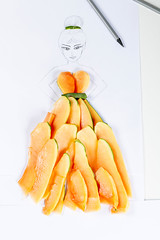 Drawing - sketch of a girl in a dress made of papaya slices on a white background with pencils