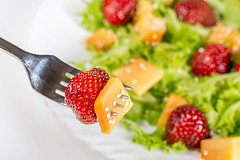 Close-up, mango and strawberry slices on a fork with sesame seeds