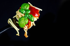 Spaghetti wound on a fork with red sauce and basil leaves on a black background