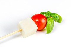 Mozzarella, red cherry tomato and basil leaves on a wooden stick