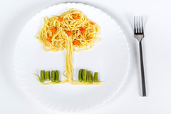 Spaghetti with vegetables in the shape of a tree. Lunch for a child on a white background, top view