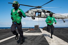 Sailors aboard USS Theodore Roosevelt (CVN 71) move away from an MH-60S Sea Hawk helicopter.
