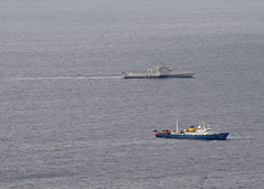 USS Gabrielle Giffords (LCS 10), top, conducts routine operations in the vicinity of a Chinese vessel.