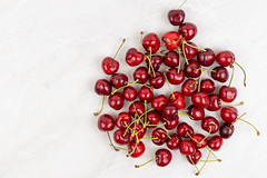 Cherries pile on the grey kitchen table with copy space