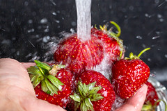 Close up, the hand with the strawberries under running tap water