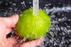 A stream of water pours onto fresh lime, close-up