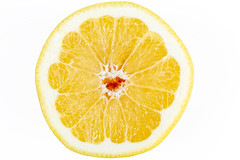 Half of a ripe yellow grapefruit on a white background