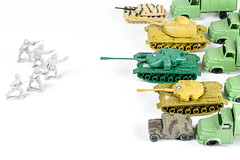 Plastic soldiers and tanks on a white background. Concept of combat operations
