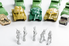 Group of plastic soldiers surrounded by enemy tanks and cars