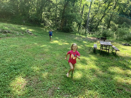 The twins run around playing at camp