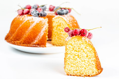 Close-up, a piece of yellow cake with red currant berries