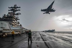 An F/A-18E Super Hornet flies over the aircraft carrier USS Ronald Reagan (CVN 76).