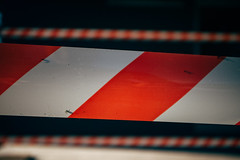 Close-up picture of red and white striped barricade tape, warning sign