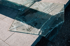 Broken glass on the tile floor. An accident at a construction site