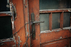 Old rustic and abandoned house, close-up shot of doors with metal wire, grunge texture