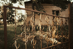 Rustic metal fence with abandoned blurry house in background