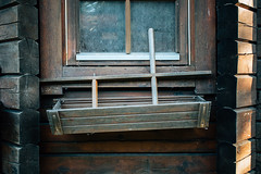 Close-up shot of rustic and old cabin window with old broken flowerpot
