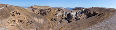 Panoramic photo of the volcanic landscape on Santorini: tourists taking a walk around the crater