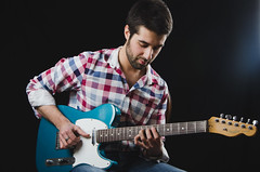 Portrait of a male model in colorful shirt playing guitar
