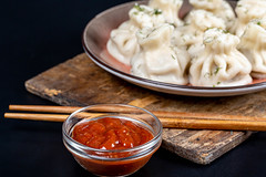 Satsebeli sauce and boiled khinkali on a dark background with chopsticks