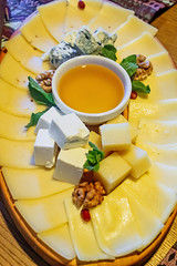 Cheese slices of different types with honey, mint leaves and walnuts