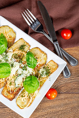 Baked zucchini with suluguni cheese, mozzarella and fresh basil leaves